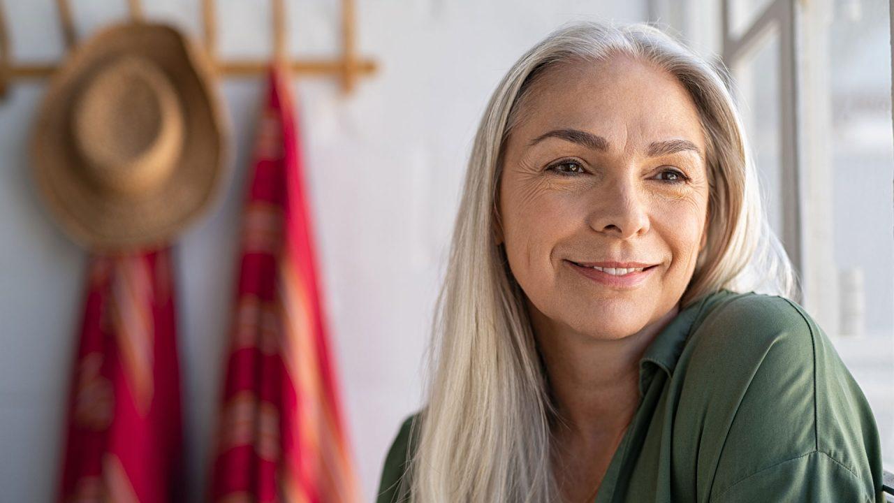 Smiling older woman using dermal filler to target facial lines and wrinkles